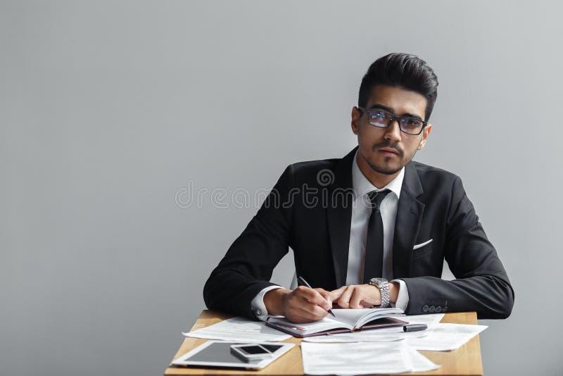 Scrittura dell'uomo d'affari in un taccuino ed esaminare macchina fotografica su un fondo grigio immagini stock