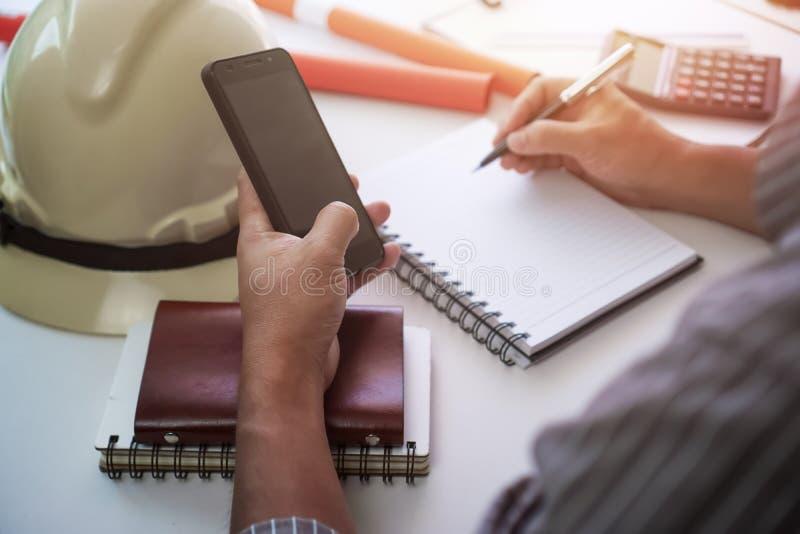 Scrittura dell'uomo sul blocco note e sul telefono usando fotografia stock