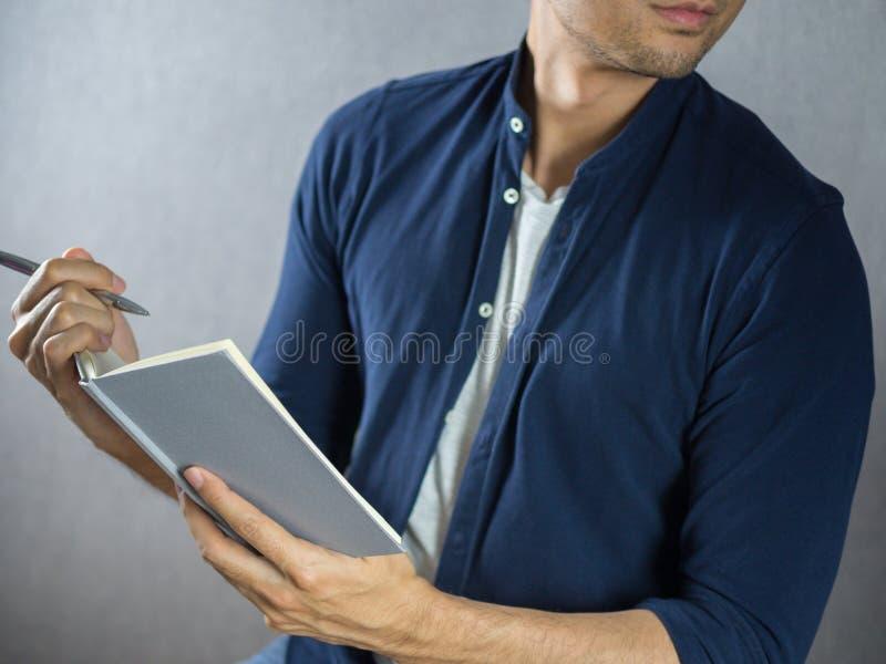 Scrittura dell'uomo sulla fine del taccuino su fotografia stock