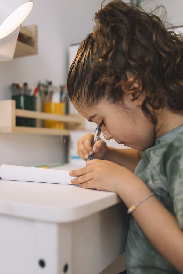 Scrittura della bambina nello scrittorio della sua stanza immagini stock