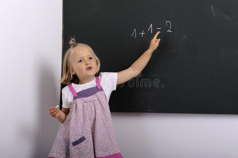 Scrittura della bambina su una lavagna fotografia stock