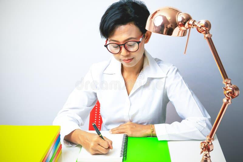 Scrittura della donna in blocco note a spirale disposto sul desktop luminoso immagini stock
