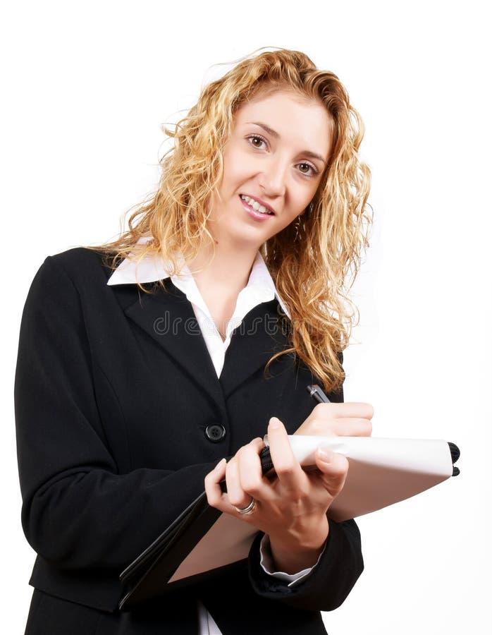 Scrittura della donna di affari sul suo blocchetto per appunti fotografia stock libera da diritti