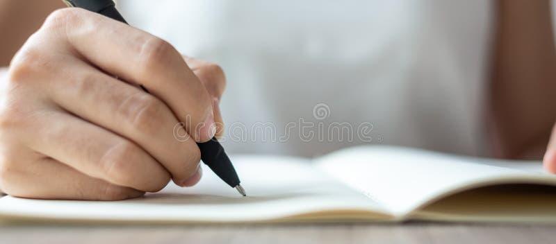 Scrittura della donna di affari sul taccuino in ufficio, mano della penna di tenuta della donna con la firma sul rapporto della c fotografia stock libera da diritti