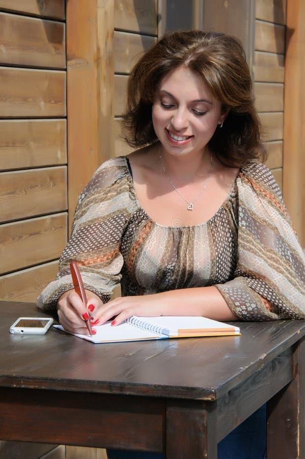 Scrittura della donna qualcosa al taccuino facendo uso della penna fotografie stock libere da diritti
