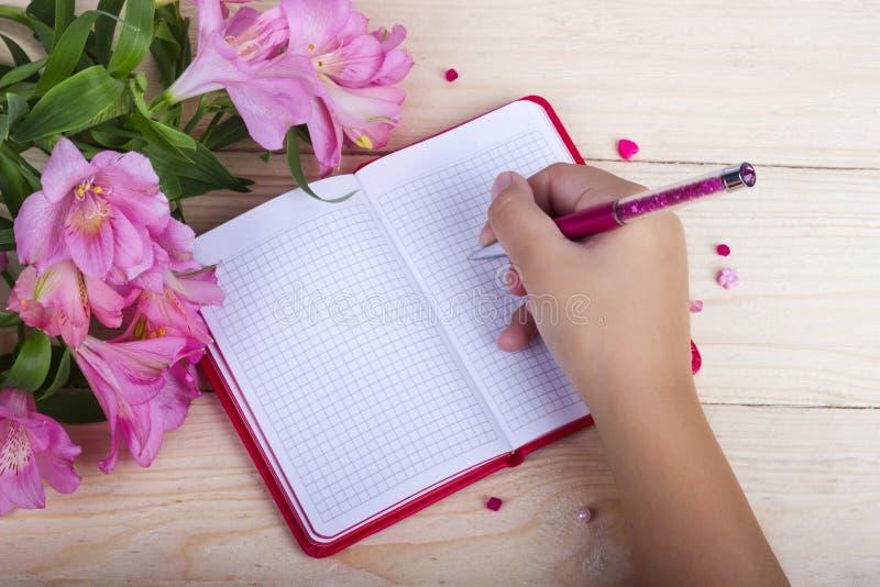 Scrittura della donna sul taccuino in bianco sulla tavola di legno immagine stock libera da diritti