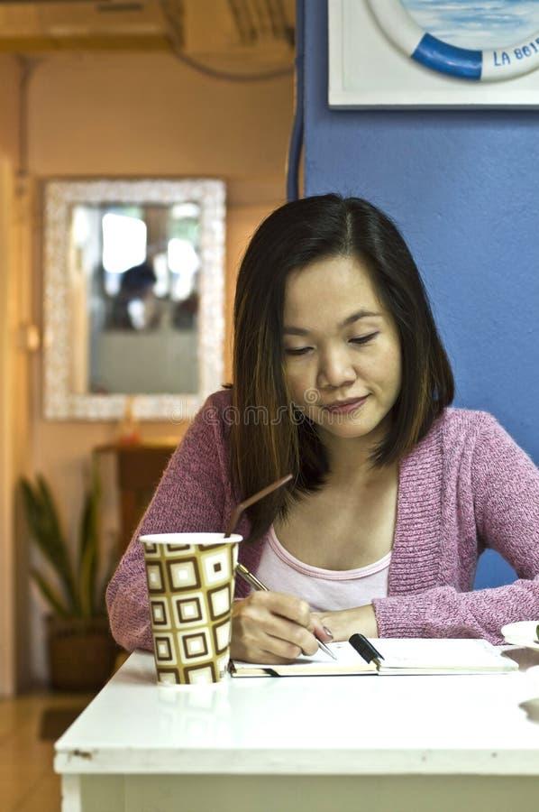 Scrittura della giovane donna al caffè fotografia stock