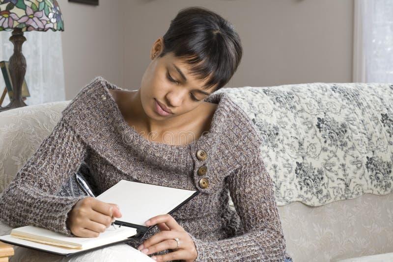Scrittura della giovane donna in libro immagini stock libere da diritti