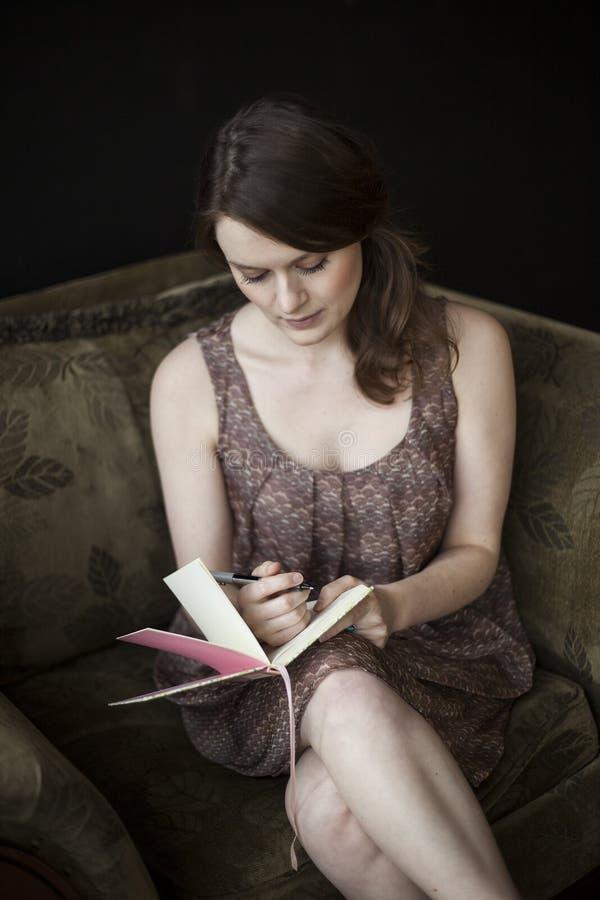 Scrittura della giovane donna in suo giornale fotografia stock