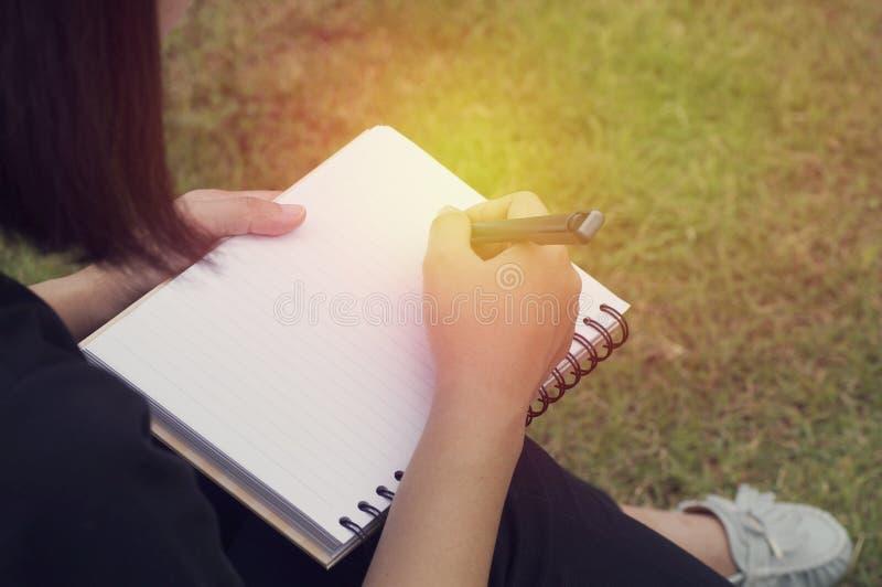 Scrittura della mano del ` s della ragazza sul diario fotografia stock libera da diritti