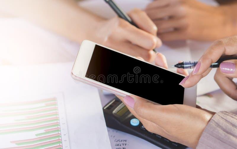 Scrittura della mano della donna di affari due e telefono cellulare usando per il loro lavoro che analizza sul progetto finanziar immagine stock