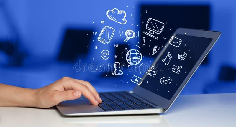 Scrittura della mano sul computer portatile con le icone di media fotografia stock libera da diritti