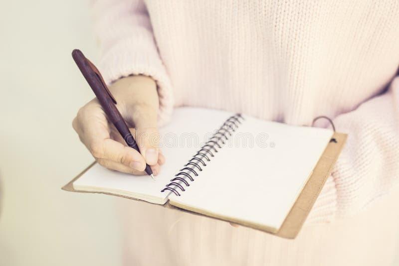 Scrittura della ragazza con la penna in diario in bianco fotografia stock libera da diritti