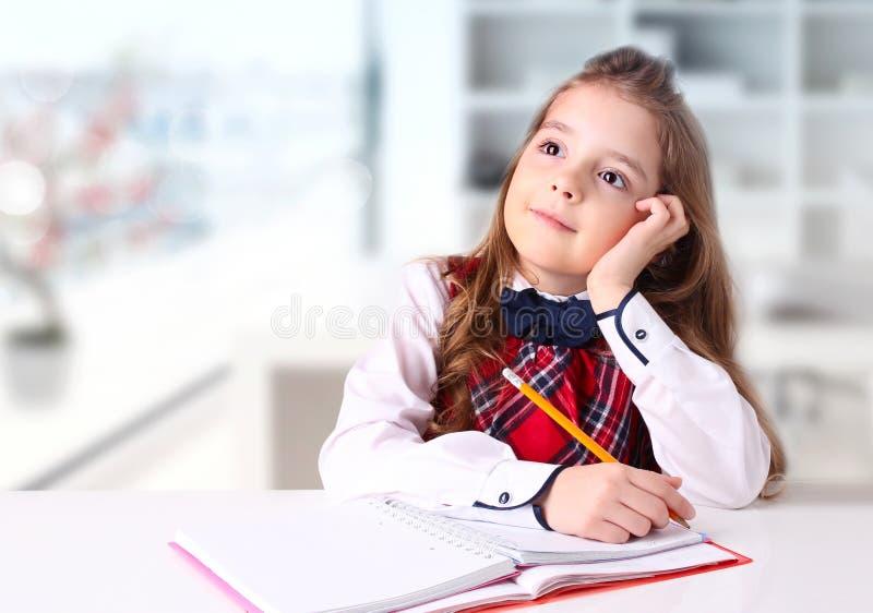 Scrittura della ragazza della scuola dello scrittorio al fondo all'interno immagini stock