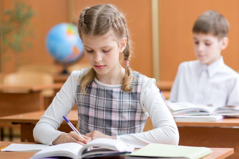 Scrittura della ragazza della scuola in taccuino in aula immagine stock libera da diritti