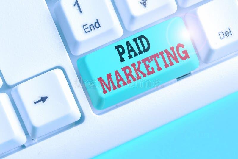 Scrittura di una nota con Paid Marketing I rivenditori di fotografia aziendale pagano al proprietario dello spazio pubblicitario  fotografia stock libera da diritti