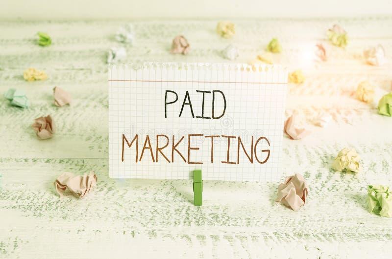 Scrittura di una nota con Paid Marketing I rivenditori di fotografia aziendale pagano al proprietario dello spazio pubblicitario  fotografie stock libere da diritti