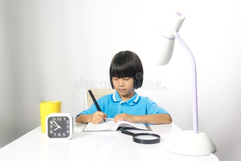 Scrittura e funzionamento svegli del bambino sullo scrittorio del lavoro immagini stock libere da diritti