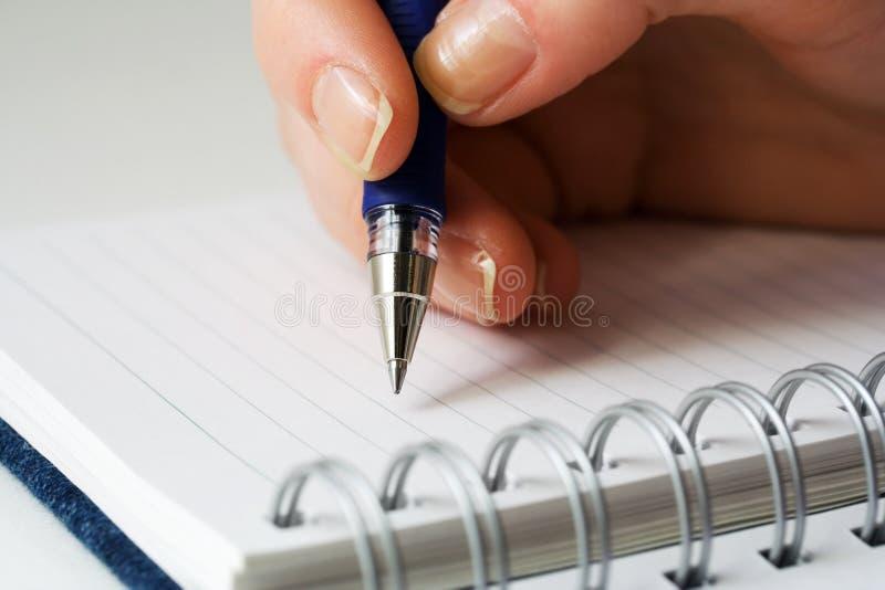 Scrittura femminile della mano alla pagina. immagini stock
