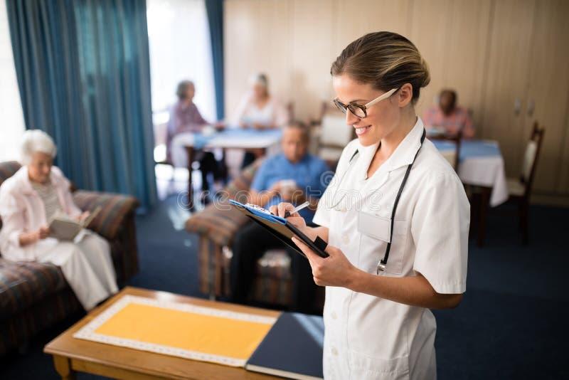 Scrittura femminile sorridente di medico nell'archivio contro la gente senior immagini stock