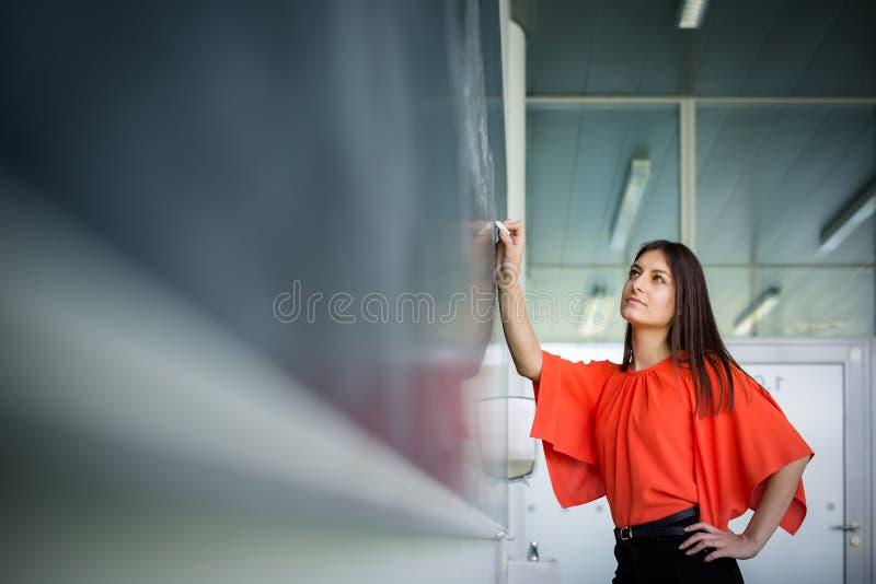 Scrittura graziosa e giovane dello studente di college sulla lavagna fotografia stock libera da diritti