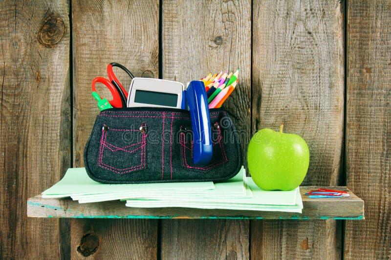 Scrittura-libri, strumenti della scuola e una mela immagini stock libere da diritti