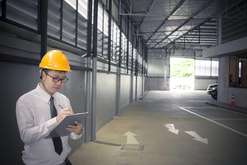 Scrittura maschio dell'ingegnere nella fabbrica con la nota sul blocco note o sul fondo vago industria immagini stock libere da diritti