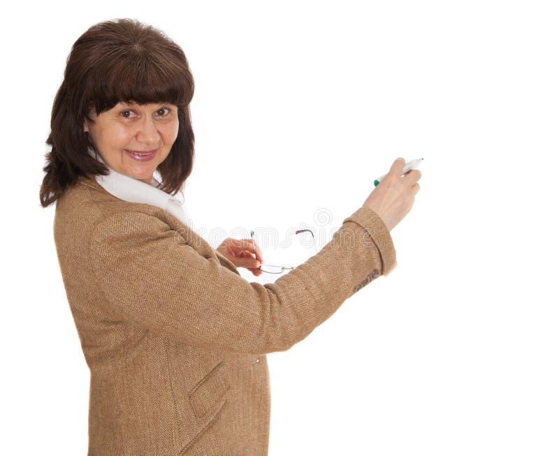 Scrittura matura della bella donna di età sul bordo bianco fotografia stock libera da diritti