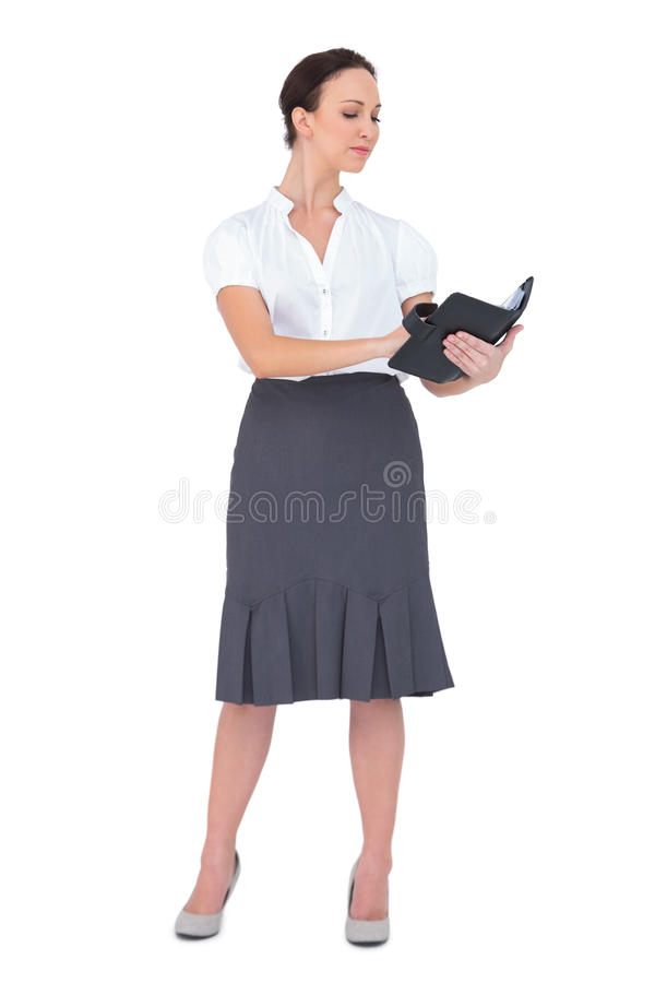 Scrittura messa a fuoco della donna di affari sul suo datebook immagine stock libera da diritti