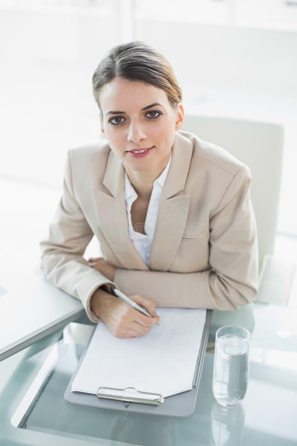 Scrittura morbidamente sorridente della donna di affari su una lavagna per appunti che esamina macchina fotografica immagine stock