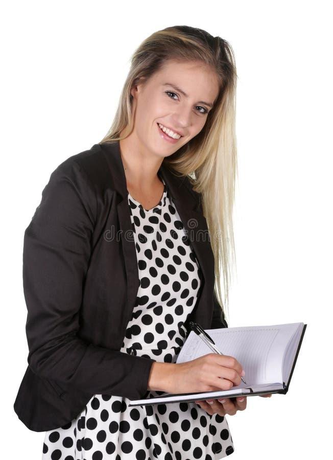 Scrittura sorridente adorabile della donna in diario immagine stock