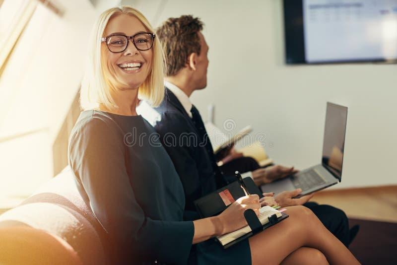 Scrittura sorridente della donna di affari in un organizzatore durante l'ufficio p fotografie stock