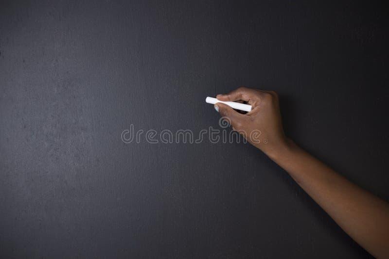 Scrittura sudafricana o afroamericana dell'insegnante della donna sul bordo nero fotografia stock