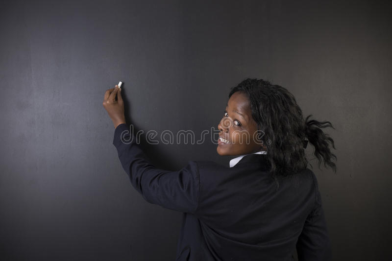 Scrittura sudafricana o afroamericana dell'insegnante della donna sul fondo del bordo del nero del gesso immagine stock