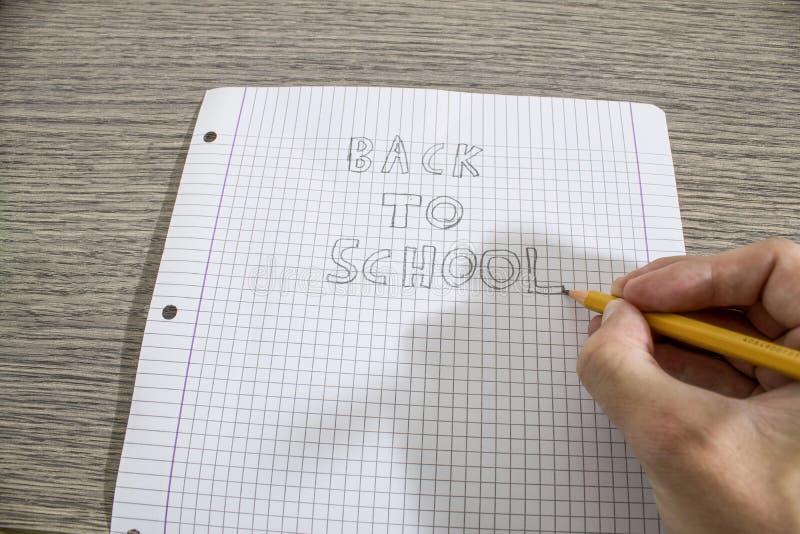 Scriva di nuovo alla scuola scritta a mano su una carta immagine stock