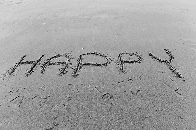Scriva la parola felice sulla spiaggia di sabbia fotografia stock