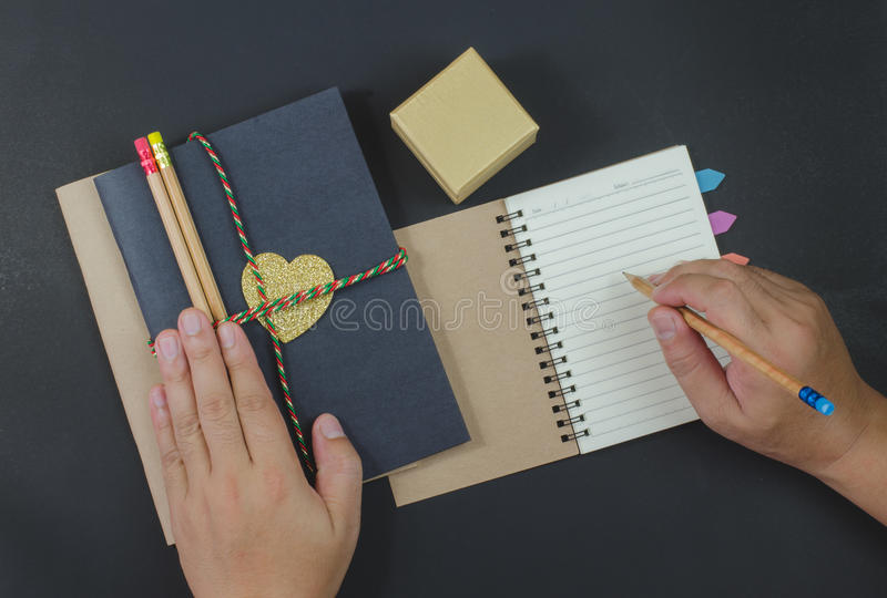 Scriva le matite di carta del taccuino su fondo nero immagine stock