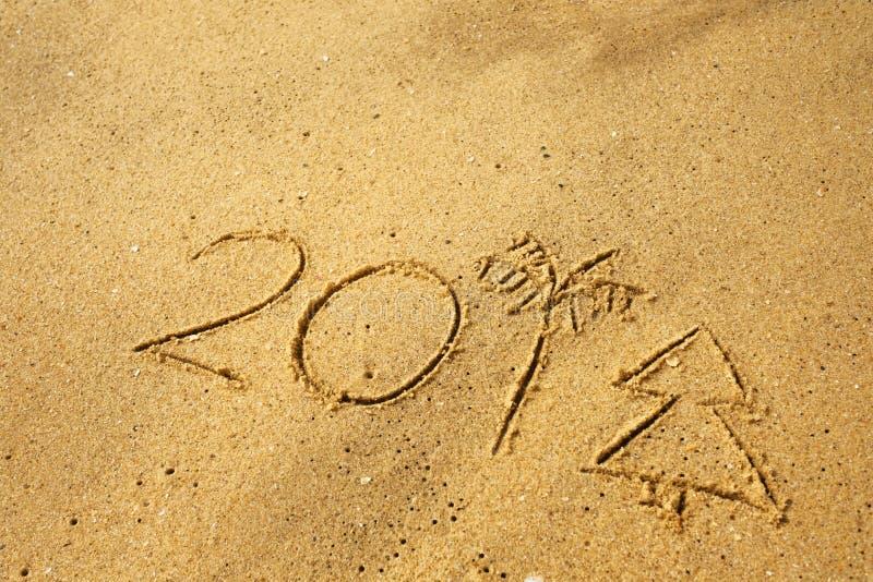 Scriva 2018 su una sabbia della spiaggia Ultimi numeri che assomigliano all'albero di Natale e della palma fotografia stock libera da diritti