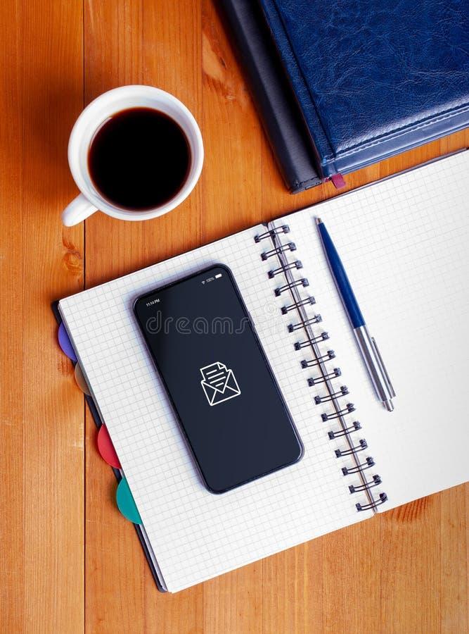 Scrivania con i libri, il blocco note aperto, il telefono cellulare e la tazza di caffè fotografia stock libera da diritti