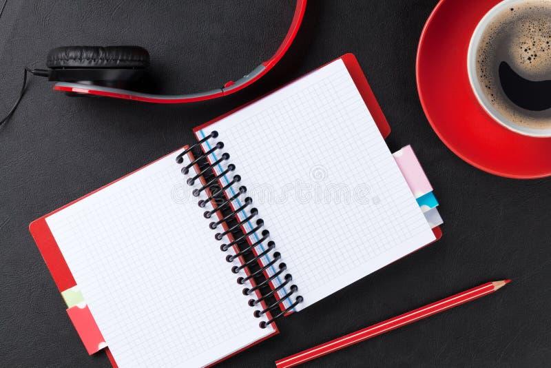 Scrivania con il blocco note, il caffè e le cuffie fotografia stock