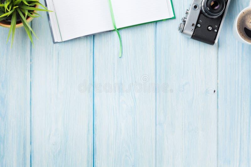 Scrivania con il blocco note, la macchina fotografica, il caffè ed il fiore fotografie stock
