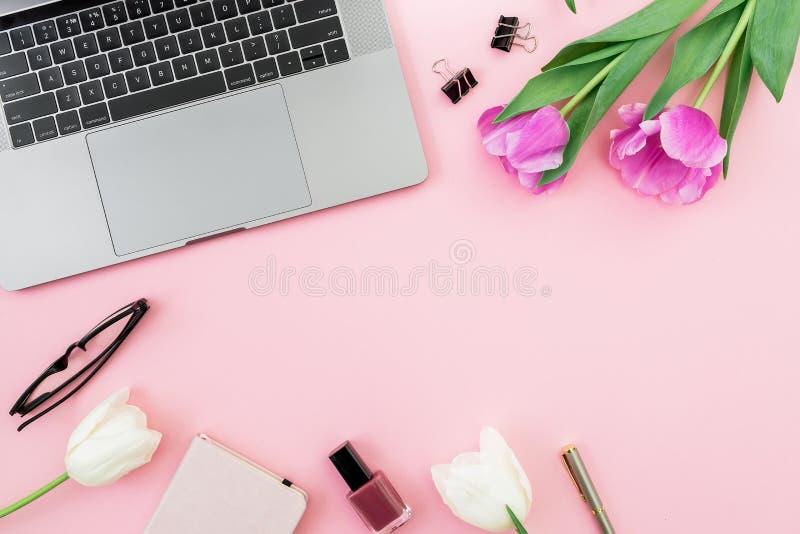 Scrivania con il computer portatile, i fiori del tulipano, i cosmetici, i vetri e la penna su fondo rosa Disposizione piana Vista fotografia stock