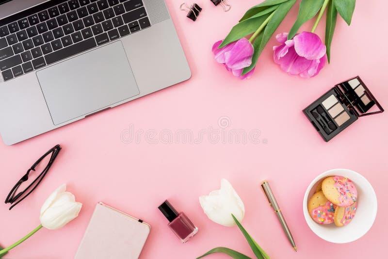 Scrivania con il computer portatile, i fiori del tulipano, i cosmetici, i vetri, la penna ed i biscotti su fondo rosa Disposizion fotografia stock