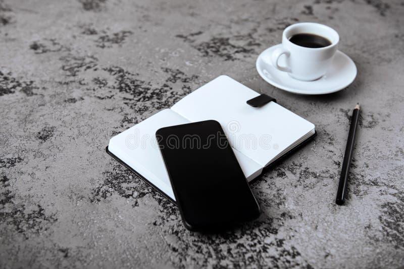 Scrivania con la tazza dello smartphone, della penna, del taccuino e di caffè dello schermo in bianco sulla tavola grigia fotografia stock libera da diritti