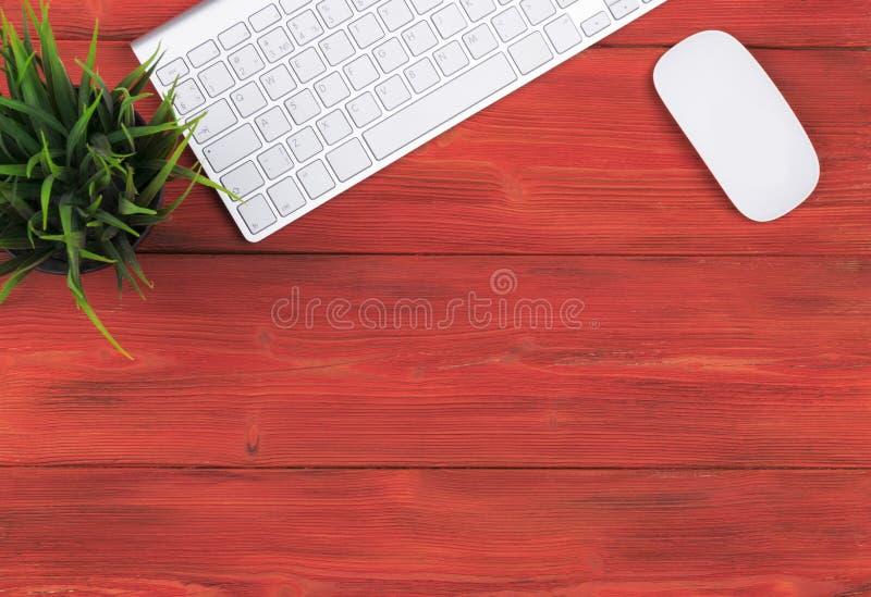 Scrivania con lo spazio della copia Dispositivi tastiera e topo senza fili di Digital sulla tavola di legno rossa, vista superior immagine stock