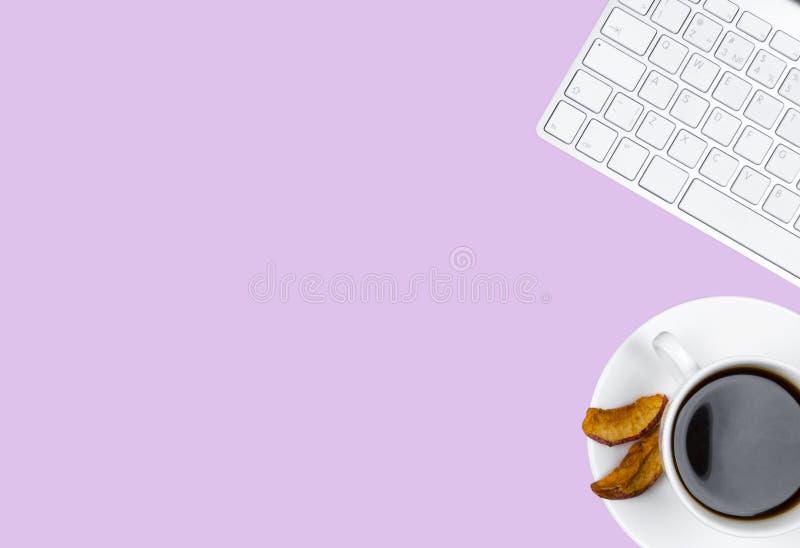 Scrivania con lo spazio della copia Dispositivi tastiera senza fili e topo di Digital isolati su fondo porpora con la tazza di ca fotografia stock