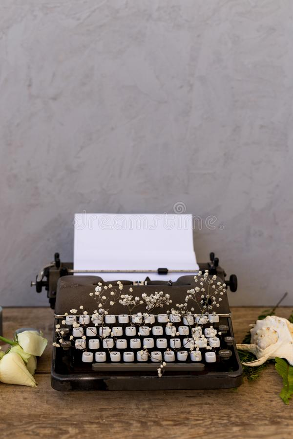 Scrivendo e freelance il concetto Macchina da scrivere d'annata con i fiori immagini stock libere da diritti