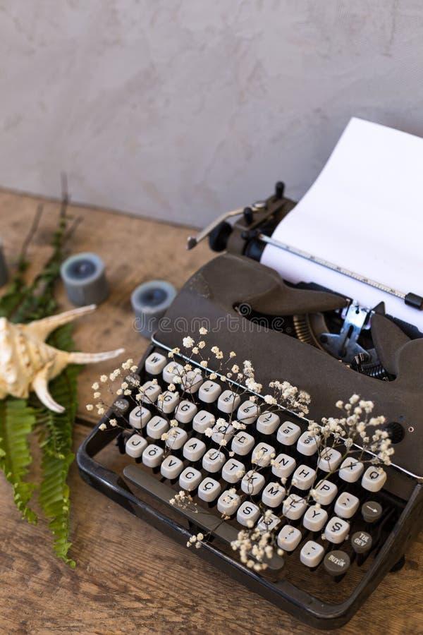 Scrivendo e freelance il concetto Macchina da scrivere d'annata con i fiori b fotografia stock libera da diritti
