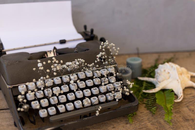 Scrivendo e freelance il concetto Macchina da scrivere d'annata con i fiori b fotografie stock