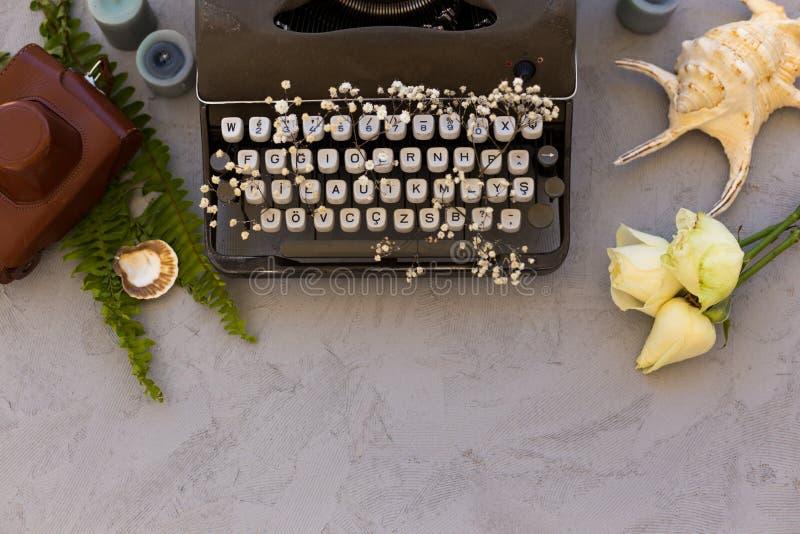Scrivendo e freelance il concetto Macchina da scrivere d'annata con i fiori b immagine stock